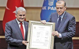 Ο Τούρκος πρωθυπουργός Μπιναλί Γιλντιρίμ παραδίδει στον πρόεδρο της χώρας Ταγίπ Ερντογάν κορνιζαρισμένο αντίγραφο της κομματικής του ταυτότητας κατά τη χθεσινή τελετή, στα κεντρικά γραφεία του κυβερνώντος Κόμματος Δικαιοσύνης και Ανάπτυξης (ΑΚΡ), στην Αγκυρα.