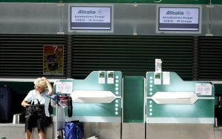 A woman sits on an empty check-in counter at Fiumicino's International Airport, in Rome, Monday Sept. 18, 2006. Pilots, flight attendants and ground workers at Alitalia took part in a four-hour strike expected to cause traffic disruption. The walkout was scheduled to begin at 12:30 p.m. (10:30GMT) across the country. Last week, a strike forced the Italian airline to scrap 179 flights. (AP Photo/Alessandra Tarantino)