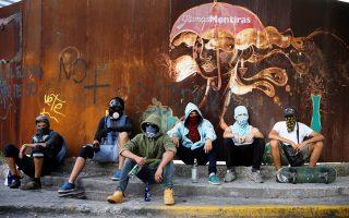 «Τα τελευταία ψέματα» γράφει το σύνθημα στον τοίχο, πίσω από τους αντικυβερνητικούς διαδηλωτές στο Καράκας.