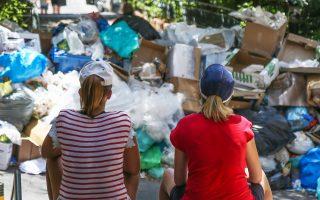 Τουρίστριες στην Αθήνα ατενίζουν τα σκουπίδια που «κοσμούν» τους δρόμους εδώ και έντεκα ημέρες.