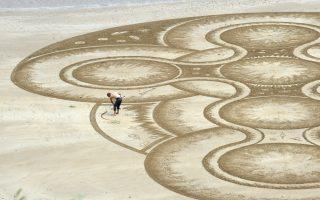 Εφήμερος καμβάς. Πάνω στην άμμο της  παραλίας στο Tendy της Ουαλίας, φτιάχνει τα έργα του ο Marc Treanor, με υπομονή και εντυπωσιακή συμμετρία.  REUTERS/Rebecca N