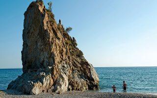 Oι πιο τολμηροί βουτούν  από την κορυφή του βράχου  στην παραλία Μελίντα. (Φωτογραφία: ΒΑΓΓΕΛΗΣ ΖΑΒΟΣ)