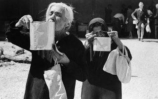 Δύο ηλικιωμένες Ροδίτισσες γυναίκες σιγοπίνουν τη σούπα που τους έχει παραχωρήσει το τοπικό κλιμάκιο του Ερυθρού Σταυρού, ένα μήνα μετά το τέλος της γερμανικής κατοχής των Δωδεκανήσων, το 1944. (AP Photo)