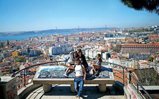 Τουρίστριες  φωτογραφίζονται στο ύψωμα Miradouro da Senhora do, με την προνομιακή θέα στη Λισαβόνα. (Φωτογραφία: AP Photo/Francisco Seco)