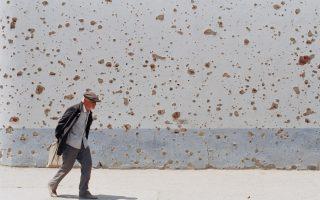 Ένας άνδρας περνάει μπροστά από έναν τοίχο που επιδεικνύει με έντονο τρόπο την εμπόλεμη κατάσταση που επικρατεί στο Γκρόζνι, την τσετσενική πρωτεύουσα, κατά τον πρώτο πόλεμο της Τσετσενίας, το 1995, καθώς οι σφαίρες και οι όλμοι έχουν αφήσει εμφατικά το ανεξίτηλο σημάδι τους. (AP Photo/Misha Japaridze)