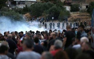 Άνδρες των ΜΑΤ ρίχνουν δακρυγόνα για να απωθήσουν το πλήθος που πορεύτηκε προς τον οικισμό των Ρομά στο Μενίδι κατά τη διάρκεια πορείας διαμαρτυρίας, μετά τον τραγικό θάνατο του 11χρονου μαθητή, από αδέσποτη σφαίρα.
