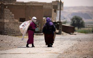 Με λευκές σημαίες ανά χείρας, δύο γυναίκες αναζητούν ασφαλές καταφύγιο στα δυτικά περίχωρα της Ράκα.