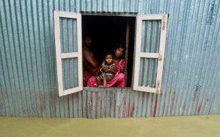 Μια γυναίκα και ένα παιδί κοιτούν έξω από το παράθυρο του σπιτιού τους, στα περίχωρα της Αγκαρτάλα στην Ινδία.