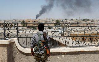 Μαχητής του YPG κοιτάει τον καπνό από τις συμμαχικές επιδρομές στη Ράκα της Συρίας.