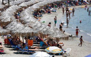 Στιγμές δροσιάς για τους λουομένους σε παραλία της Σαρωνίδας.
