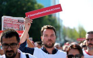 Πινακίδα με το σύνθημα «Η δημοσιογραφία δεν είναι έγκλημα» κρατάει αυτός ο διαδηλωτής.