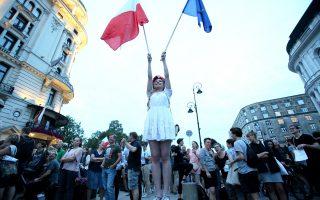 Πολωνοί πολίτες συμμετέχουν στις κινητοποιήσεις της αντιπολίτευσης κατά του νόμου.