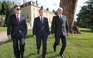 Ο πρόεδρος Εμανουέλ Μακρόν εν μέσω του πρωθυπουργού της Λιβύης Φαγέζ αλ Σαράζ και του στρατηγού Χαλίφα Χαφτάρ.