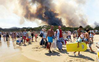 Παραθεριστές απομακρύνονται από την παραλία Λαβαντού στην Κυανή Ακτή, μετά το ξέσπασμα φωτιάς σε δασική ζώνη της περιοχής. Περισσότερα από 12.000 άτομα αναζήτησαν καταφύγιο από τις πυρκαγιές που κατέκαψαν πάνω από 10.000 στρέμματα στον νομό Βαρ στη νότια Γαλλία.