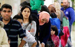 Πρόσφυγες στο αεροδρόμιο «Ελ. Βενιζέλος» περιμένουν να επιβιβαστούν. Λιγότεροι από 100 αιτούντες άσυλο μεταφέρονται, τονίζουν οι ΜΚΟ.