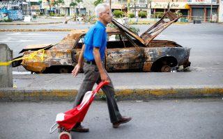 Ενας άνδρας περνάει μπροστά από οδόφραγμα στο Καράκας στη διάρκεια της γενικής απεργίας.