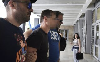 A Russian man, centre, is escorted by police officers as he arrives at a courthouse at the northern Greek city of Thessaloniki, on Wednesday, July 26, 2017. Greek authorities say they have arrested a Russian man wanted in the United States on suspicion of masterminding a money laundering operation involving at least $4 billion through bitcoin transactions. (AP Photo/Giannis Papanikos)
