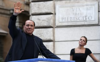 Former Italian Prime Minister Silvio Berlusconi waves to supporters as his girlfriend Francesca Pascale looks on during a rally to protest his tax fraud conviction, outside his palace in central Rome August 4, 2013. Tensions in Italy's squabbling coalition heightened ahead of a rally by supporters of Silvio Berlusconi in Rome on Sunday in protest at a tax fraud conviction that threatens his future in politics and the fragile government.   REUTERS/Alessandro Bianchi   (ITALY - Tags: POLITICS CIVIL UNREST)