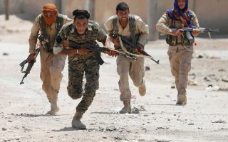 Ανδρες της κουρδικής πολιτοφυλακής YPG τρέχουν σε δρόμο στη Ράκα της Συρίας, στην οποία κατάφεραν να διεισδύσουν πριν από λίγες ημέρες.
