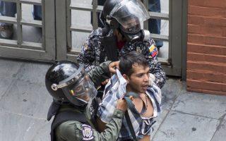 Ανδρες της Εθνοφρουράς συλλαμβάνουν διαδηλωτή έξω από τα γραφεία της δημόσιας τηλεόρασης της Βενεζουέλας, στο Καράκας.