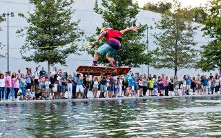 Μερικά μέτρα πάνω από τη στάθμη του νερού του καναλιού του Κέντρου Πολιτισμού  Ίδρυμα Σταύρος Νιάρχος, ο Έλληνας πρωταθλητής του θαλάσσιου σκι Νίκος Πλυτάς επιδίδεται σε μια σειρά ριψοκίνδυνων αλμάτων - το Wakeboard Show ήταν μία από τις 75 εκδηλώσεις του πρώτου Summer Nostos Festival, που προσέλκυσε το ενδιαφέρον 140.000 επισκεπτών! Απόδειξη ότι οι Αθηναίοι θέλουν να είναι δραστήριοι και να μην περνούν τις μέρες τους κάτω από το κλιματιστικό τους.  Το επταήμερο SNF 2017, ένα πρωτότυπο και πολυσυλλεκτικό διεθνές φεστιβάλ τέχνης, άθλησης και εκπαίδευσης, ήταν η πρόταση του ΚΠΙΣΝ για την έναρξη του φετινού καλοκαιριού. Θα ακολουθήσει ένα γεμάτο πρόγραμμα για τους καλοκαιρινούς μήνες, με συναυλίες, εκθέσεις και κάθε λογής εκδηλώσεις στους χώρους του Ιδρύματος, που έχει κερδίσει, απολύτως λογικά, το να θεωρείται πλέον βασικό σημείο αναφοράς στα δρώμενα της πόλης.  Ωραία ιδέα και οι προβολές ταινιών τις τρεις προσεχείς Παρασκευές στο πλαίσιο του «Park your Cinema». © ΙΣΝ/Αγγελος Χριστοφιλόπουλος