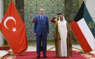 Turkey's President Recep Tayyip Erdogan, left, stands to attention with Emir of Kuwait Sheikh Sabah Al Ahmad Al Sabah during his departure ceremony in Kuwait City, Kuwait, Monday, July 24, 2017. Erdogan later flew to Qatar on the final leg of a Gulf two-day tour, which also took him to already took him to Saudi Arabia, aimed at forging a resolution to the diplomatic standoff gripping the Gulf nation and four fellow Arab countries (Presidency Press Service/Pool Photo via AP)