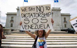 «Οχι στη δικτατορία, SOS για τη Βενεζουέλα» είναι το σύνθημα της διαδηλώτριας.