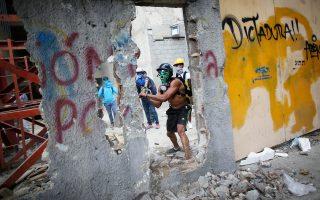 Μασκοφόροι αντικυβερνητικοί διαδηλωτές γκρεμίζουν τοίχο, προκειμένου να εφοδιαστούν με πολεμοφόδια για τις συγκρούσεις τους με τις κυβερνητικές δυνάμεις.