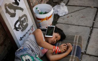 STEREO. Με το κινητό κολλημένο στο αυτί για να ακούει μουσική ενώ με ένα δεύτερο παίζει παιχνίδια περνά την ώρα του στον καταυλισμό των εγχώριων μεταναστών-εργατών στα περίχωρα του Πεκίνου. REUTERS/Thomas Peter