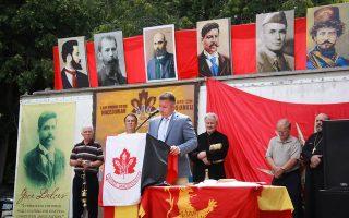 Στο φόντο φαίνονται χάρτης της «Μεγάλης Μακεδονίας» και σημαία με αστέρι της Βεργίνας