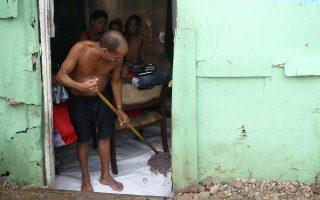 Ενας άνδρας σφουγγαρίζει σε γειτονιά του Σάντο Ντομίνγκο.