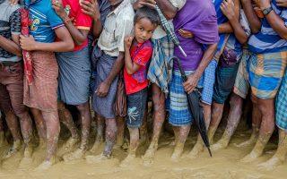Μικρά παιδιά, μέλη της μειονότητας των Ροχίνγκια, περιμένουν το συσσίτιο σε προσφυγικό καταυλισμό του Μπανγκλαντές.