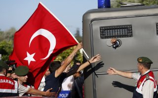 Protesters run after a prison van as an unidentified defendant sticks his fist out as he's driven to a courthouse in Silivri, where a hearing for people charged with attempting to overthrow Prime Minister Tayyip Erdogan's Islamist-rooted government is due to take place, August 5, 2013. A Turkish court on Monday began sentencing nearly 300 defendants accused of plotting to overthrow the government, handing prison sentences of up to 20 years to some and acquitting 21 others. The court was announcing the verdicts individually. Verdicts on high-profile defendants including former armed forces commander Ilker Basbug were yet to be announced. REUTERS/Murad Sezer (TURKEY - Tags: POLITICS CIVIL UNREST TPX IMAGES OF THE DAY)