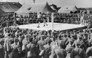 Σε ένα διάλειμμα από τους βομβαρδισμούς της Λουφτβάφε, οι Βρετανοί στρατιωτες παρακολουθούν έναν αγώνα μποξ που διεξάγεται στα πλαίσια ενός μεγάλου τουρνουά πυγμαχίας, το οποίο αποτελεί το πρώτο μεγάλο αθλητικό γεγονός του πολέμου στη Βρετανία, το 1940. (AP Photo)