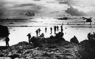 Μία ομάδα Αμερικανών πεζοναυτών τσαλαβουτά στην ακτή μίας παραλίας της Νήσου Τινιάν στον Ειρηνικό Ωκεανό, αφού αποβιβάστηκε από ένα σκάφος της αμερικανικής ακτοφυλακής, το 1944. Σκοπός τους είναι η ενίσχυση των χερσαίων δυνάμεων που επιχειρούν στο νησί. (ΑP Photo)