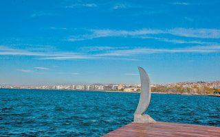 Το «Φεγγαράκι στην Ακτή», το γνωστό γλυπτό στη Νέα Παραλία Θεσσαλονίκης που κάποιοι ξήλωσαν και έριξαν στη θάλασσα γιατί τους θύμιζε την τουρκική ημισέληνο, κινδυνεύει για δεύτερη φορά να «πνιγεί», όχι πλέον στα νερά του Θερμαϊκού αλλά στην ελληνική γραφειοκρατία. Ο δήμος αποφάσισε να το τοποθετήσει πλάι στον αυτοφωτιζόμενο γυάλινο κυλινδρικό «Πύργο της Φιλίας», που θα κατασκευάσει ο Κώστας Βαρώτσος, όμως ο φάκελος με τη μελέτη για την επανατοποθέτηση ταξιδεύει ένα χρόνο τώρα σε υπηρεσίες για αλλεπάλληλες εγκρίσεις.