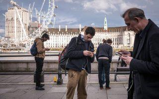 Δημοσιογράφοι και τουρίστες προσηλωμένοι στα smartphones τους κοντά στο βρετανικό κοινοβούλιο, στο Λονδίνο. Ποιος είναι ποιος;