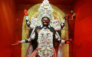 Ολα για τους θεούς. Οσο πιο λίγα έχει ένας λαός, τόσο περισσότερα σε λάμψη και πλούτο δίνει στους θεούς του. Ετσι ο καλλιτέχνης που μόλις διακρίνεται εκεί ψηλά, βάζει τις τελευταίες πινελιές στο χέρι της θεάς Kali με αφορμή το φεστιβάλ Kali Puja στην Καλκούτα. REUTERS/Rupak De Chowdhuri