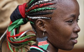 Με πάθος και πίστη. Με τα μαλλιά της στολισμένα στα εθνικά χρώματα και σκουλαρίκια ασορτί, μια νεαρή Κενυάτισσα περιμένει να ψηφίσει στο εκλογικό κέντρο της πόλης Gatundu. Οι επαναληπτικές προεδρικές εκλογές στην χώρα γίνονται εν μέσω εντάσεων αλλά και του μποϊκοτάζ του μεγαλυτέρου αντιπολιτευόμενου κόμματος. AP Photo/Ben Curtis