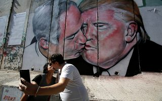 Κάτι θυμίζει. Τουριστική ατραξιόν έγινε το γκράφιτι στο τείχος της Δυτικής Οχθης, που εικονίζει τον  Αμερικανό Πρόεδρο Donald Trump και τον Ισραηλινό Πρωθυπουργό Benjamin Netanyahu να φιλιούνται.  REUTERS/Mussa Qawasma