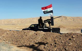 Aνδρες ιρακινής πολιτοφυλακής καταλαμβάνουν φυλάκιο στα περίχωρα της Μπασίκα, το οποίο εγκατέλειψαν οι Κούρδοι μαχητές.