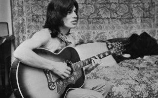 Ο Μικ Τζάγκερ, ηγέτης του βρετανικού συγκροτήματος των Ρόλινγκ Στόουνς, παίζει με την κιθάρα του κατά τη διάρκεια ενός διαλείμματος από τα γυρίσματα της ταινίας «Performance» του Νίκολας Ρεγκ, στην οποία πρωταγωνιστεί, το 1968. (AP Photo)