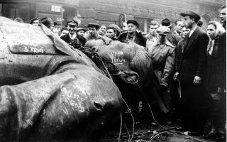 Ούγγροι πολίτες στέκονται δίπλα στο αποκαθηλωμένο από διαδηλωτές, άγαλμα του Ιωσήφ Στάλιν, το οποίο μέχρι πρότινος δέσποζε μπροστά στο Εθνικό Θέατρο της Βουδαπέστης, το 1956. Μία μέρα νωρίτερα, μία μεγάλη φοιτητική διαδήλωση κατά του σοβιετικού καθεστώτος της Λαϊκής Δημοκρατίας τη Ουγγαρίας πυροδότησε την ένοπλη αντισοβιετική εξέγερση, που έμεινε ευρύτερα γνωστή ως η Ουγγρική Επανάσταση του 1956. (AP Photo/Arpad Hazafi)