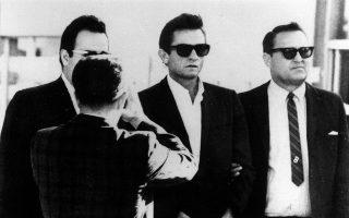 Ο αντισυμβατικός αστέρας της κάντρι και ροκ μουσικής, Τζόνι Κας, μεταφέρεται από τη φυλακή του Ελ Πάσο στο ομοσπονδιακό δικαστήριο του Τέξας, το 1965. Λίγες μέρες πριν, ο Κας συνελήφθη κατά τη διάρκεια περιοδείας στο διεθνές αεροδρόμιο της πολιτείας από άνδρες του τμήματος ναρκωτικών της αστυνομίας, λόγω υποψιών ότι εισήγαγε παράνομες ουσίες στη χώρα από το Μεξικό. Εντούτοις, ο μουσικός μετέφερε 1.000 χάπια και ηρεμιστικά, τα οποία είχε λάβει μετά από φαρμακευτική συνταγογράφηση, με αποτέλεσμα να λάβει από το δικαστήριο καταδίκη με αναστολή. (AP Photo)