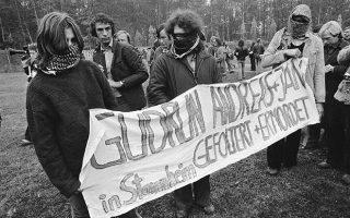 Τρεις νεαροί παρευρισκόμενοι στην κηδεία των μελών της ηγετικής ομάδας της γερμανικής ακροαριστερής τρομοκρατικής οργάνωσης Φραξία Κόκκινος Στρατός, κρατούν ένα πανό που κάνει λόγο για βασανισμό και δολοφονία των θανόντων στις φυλακές όπου κρατούνταν, το 1977. Οι νέοι έχουν καλυμμένα τα πρόσωπα τους για να μην αναγνωριστούν από τους αστυνομικούς που βρίσκονταν στην κηδεία. (AP Photo)