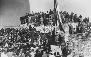 Έξι ημέρες μετά την απελευθέρωση της Αθήνας από τις γερμανικές δυνάμεις κατοχής, φτάνει στην πρωτεύουσα η εξόριστη κυβέρνηση Εθνικής Ενότητας υπό τον Γεώργιο Παπανδρέου, η οποία γίνεται δεκτή με επευφημίες και πανηγυρισμούς από τον αθηναϊκό λαό, το 1944. Την ίδια ημέρα, ο πρωθυπουργός Γεώργιος Παπανδρέου ύψωσε τη γαλανόλευκη στον Ιερό Βράχο της Ακρόπολης και εκφώνησε τον «Λόγο της Απελευθέρωσης» από την Πλατεία Συντάγματος, σε δύο από τις εμβληματικότερες στιγμές των ημερών του τέλους της κατοχής. (Φώτο: kathimerini.gr)