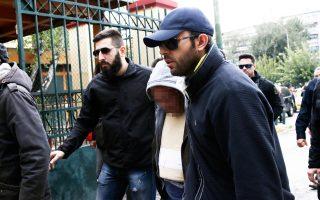 Ο 58χρονος δράστης της στυγερής δολοφονίας, κατά τη μεταγωγή του χθες στα δικαστήρια της πρώην Σχολής Ευελπίδων.