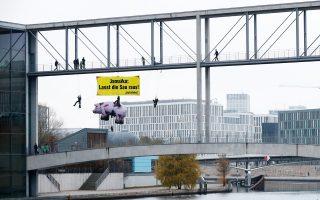 Ακτιβιστές της Greenpeace ζητούν από τους διαπραγματευτές να σεβαστούν το περιβάλλον.