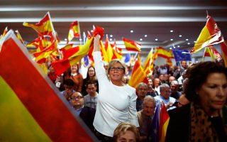 Διαδηλωτές κυματίζουν ισπανικές σημαίες στη διάρκεια ομιλίας του Ραχόι στη Βαρκελώνη.