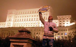 Ρουμάνα κρατάει πλακάτ με το σύνθημα «Ολοι για τη δικαιοσύνη» μπροστά στο Κοινοβούλιο, στο Βουκουρέστι.